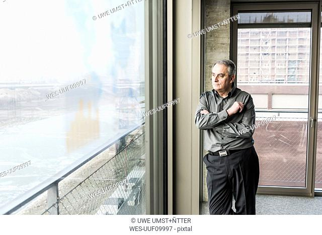 Senior businessman looking out of window
