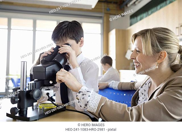 Elementary student and teacher using microscope in classroom