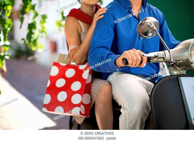 Cropped shot of young couple with shopping bags riding on moped in city