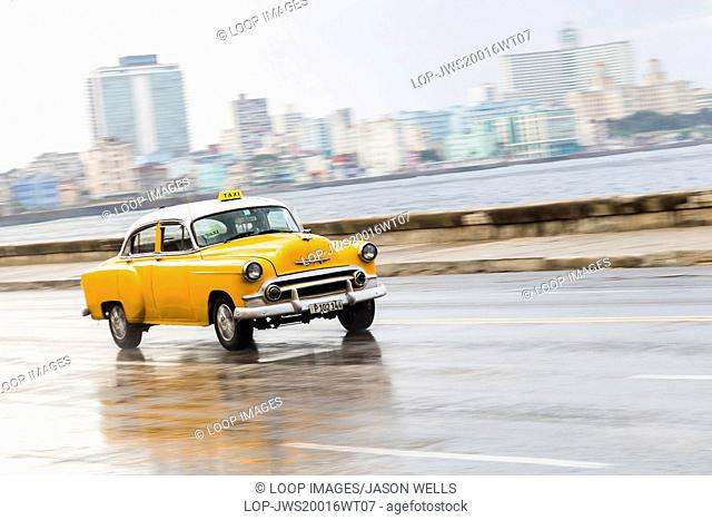 A yellow taxi travels at speed along the Malecon ocean highway in Havana