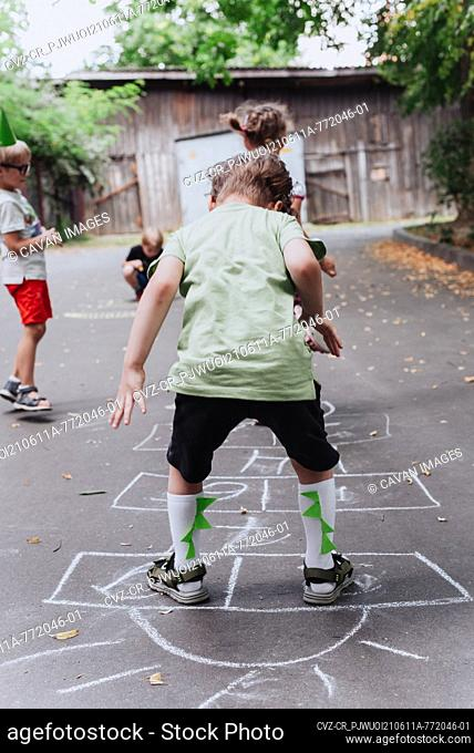 5 years old boy kid playing hopscotch outdoors, children outdoor activities, wearing green t-shirt with dinosaurus print and dino helmet