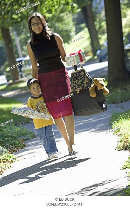 Hispanic mother and son carrying gifts