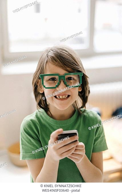 Portrait of smiling boy wearing pixel glasses holding cell phone