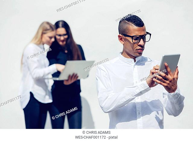 Portrait of young man with glasses using mini tablet in front of white background