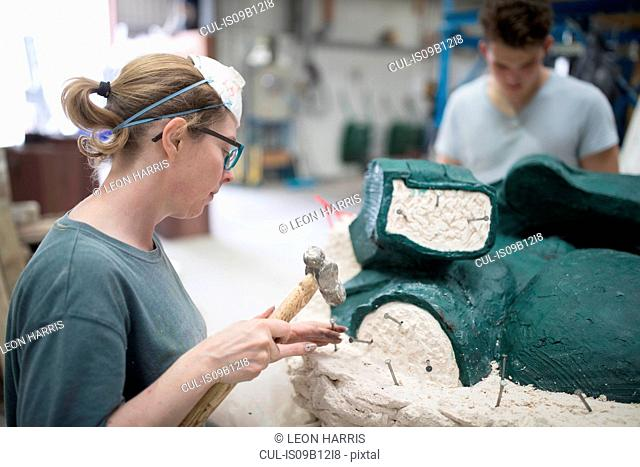 Female foundry worker removing mould from bronze sculpture in bronze foundry
