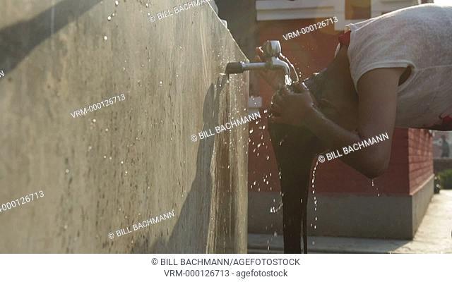 Kathmandu Nepal girl washes her hair in water spicket at childrens home in the mornin in Eastern Kathmandu, Nepal