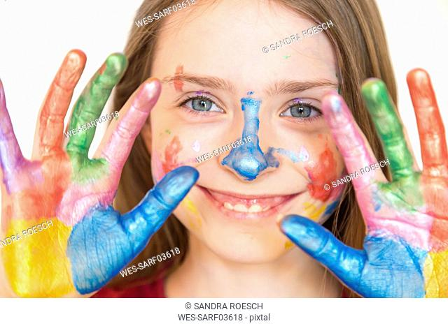 Portrait of smiling girl with finger paints on hands