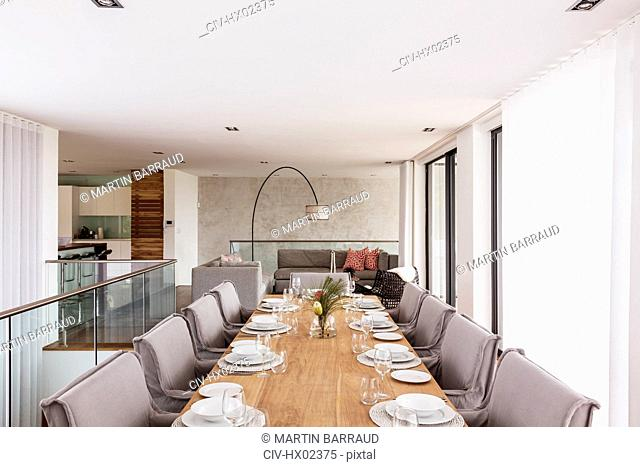 Modern, luxury home showcase interior dining room with placesettings on dining table