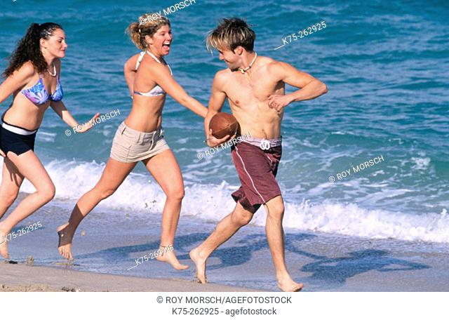 Teens play football at the beach