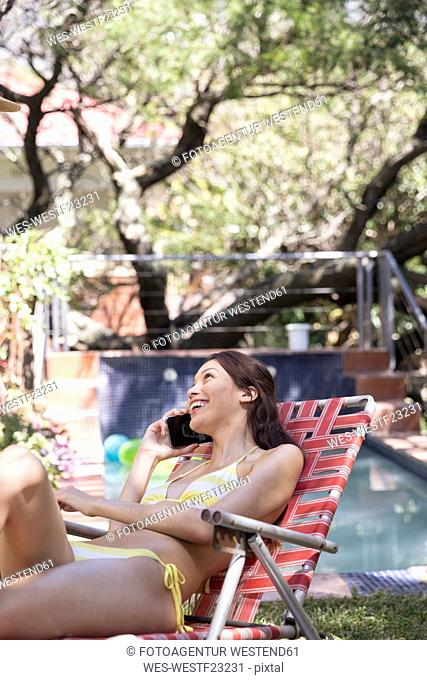 Young woman on the phone in deckchair at the poolside