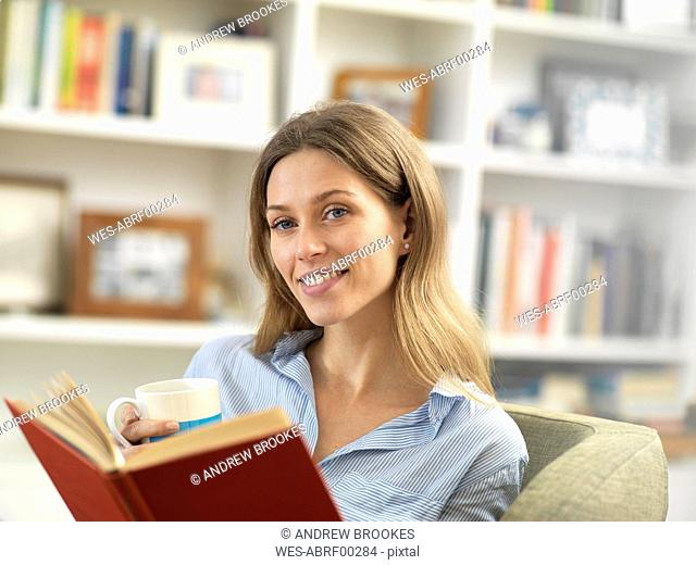 Smiling young woman relaxing at home with a hot drink and a book