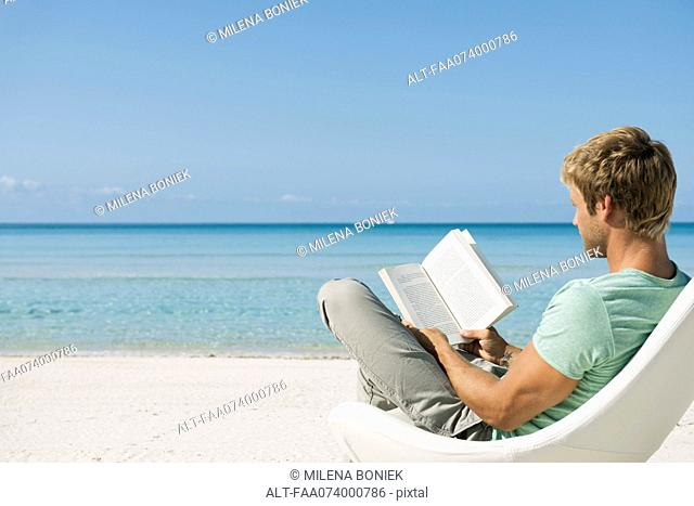 Young man reading book on beach