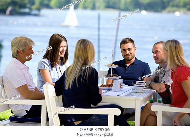 Six people having coffee beside sea