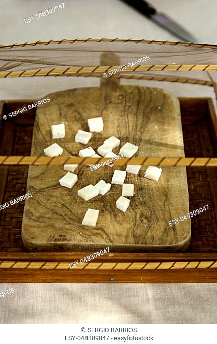 Pieces of cheese on a table for tasting, detail of milk product, fat food, delight