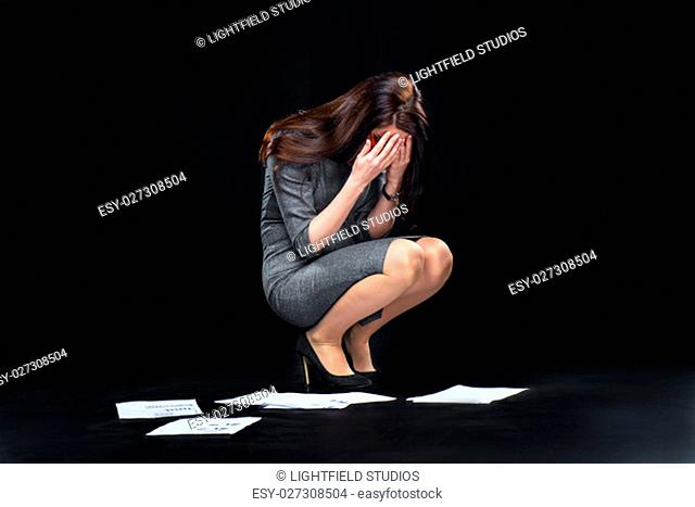 Depressed young businesswoman crying over dropped documents