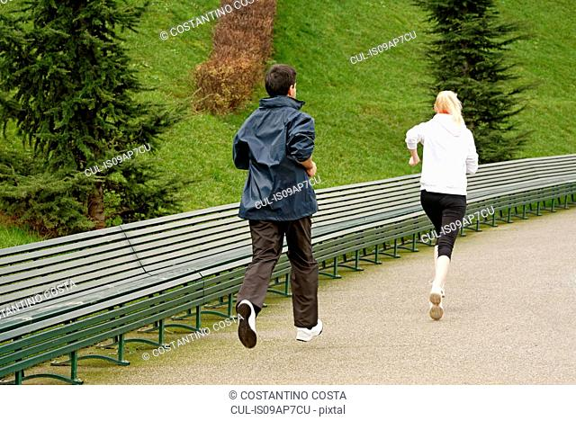 Man and woman running along pathway, rear view