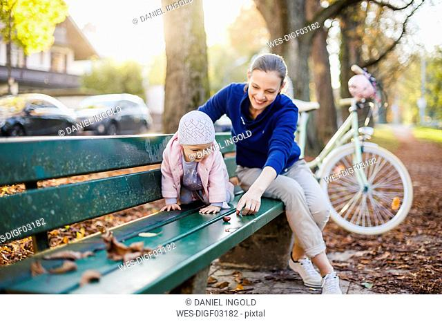 Mother and daughter taking a break on a park bench