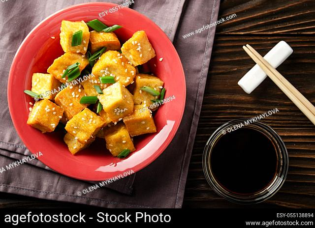 Flat lay view at crispy deep stir fried tofu cubes with chives in clay dish on wooden kitchen table with napkin and soy sauce aside