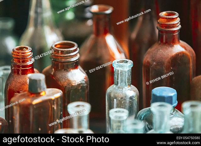 Many Old Medical Glass Capacity. Detail Of Retro Chemical Pharmaceutical Science Researches. Many Small Vintage Bottles And Glassware Different Sizes And Colors