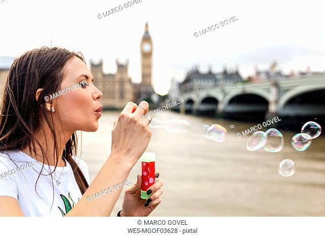 UK, London, woman making soap bubbles near Westminster Bridge