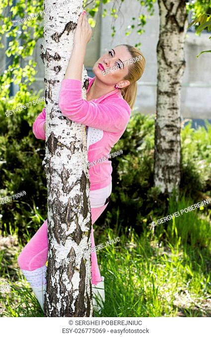 the beautiful woman in a pink suit at a birch, a subject beautiful women and seasons of the nature, a season spring, blossoming of plants