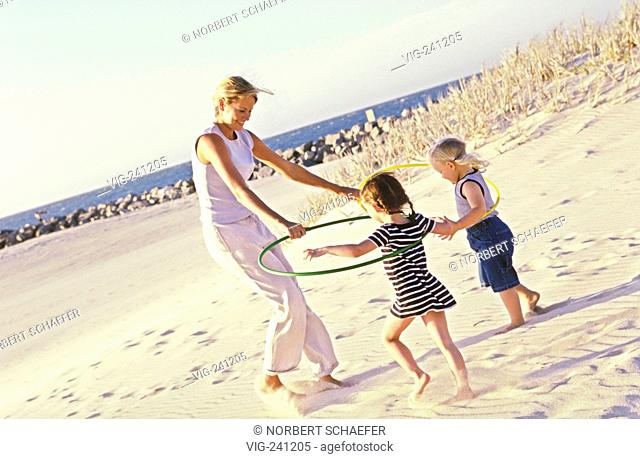 portrait, beach-scene, mother plays with her 2 3-4 years old daughters with coloured hoola hoops  - GERMANY, 28/01/2004
