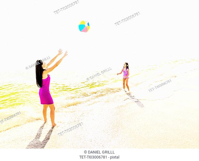 Mom throwing beach ball to her daughter (6-7) on beach