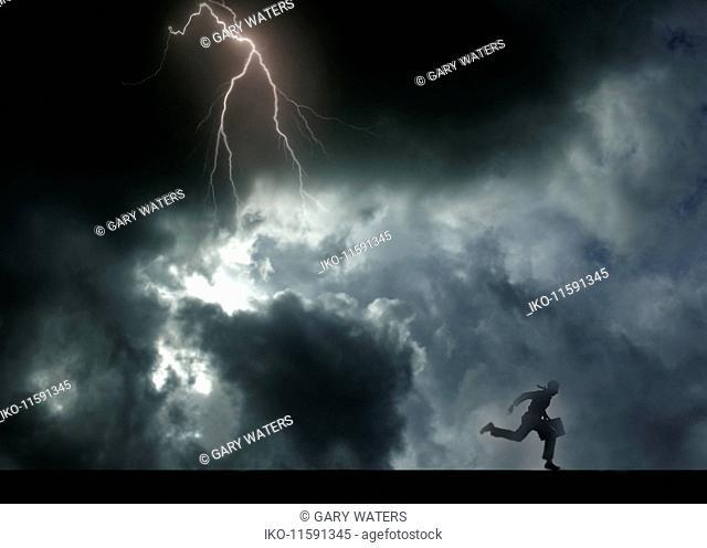 Businessman running away from storm