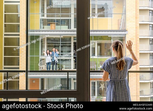 Back view of woman standing on balcony waving to her neighbours