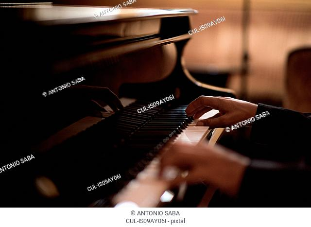 Hands of young man playing piano keys in bar at night