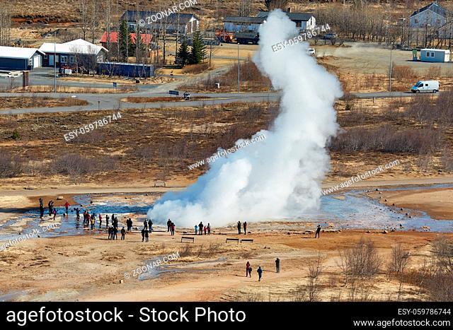 Erupting geyser in Iceland, Strokkur, spectators standing nearby