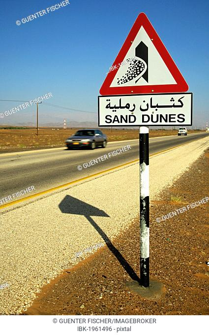 Road sign in English and Arabic warning of shifting sand dunes at a desert road, Sultanate of Oman, Middle East, Asia