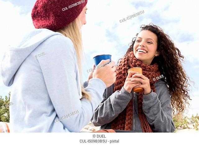 Two young women laughing at beach picnic, Western Cape, South Africa