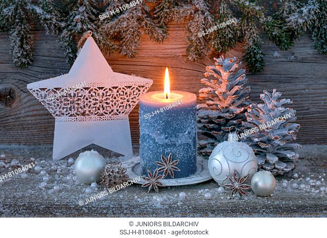 Christmas decoration: Burning candle with silver christmas baubles, cones and a star. Switzerland