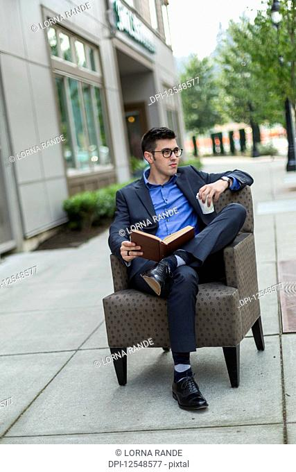 A young man sits reading a book in an armchair on an outdoor walkway and holds a cup of coffee; Bothell, Washington, United States of America