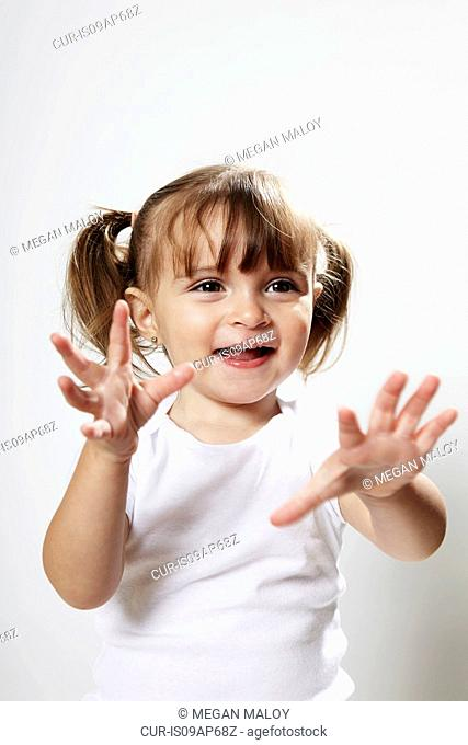 Portrait of young girl with pigtails, with hands up