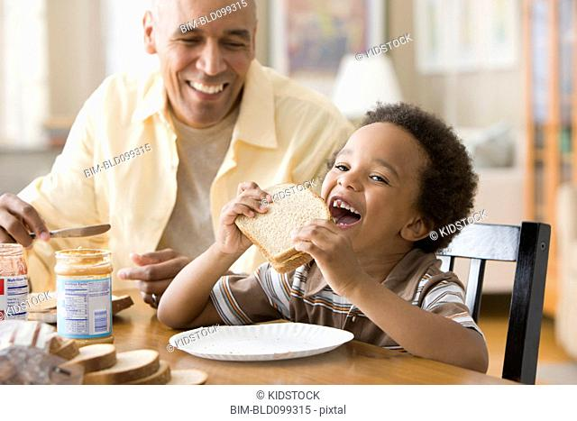 Grandfather and grandson making peanut butter and jelly sandwiches