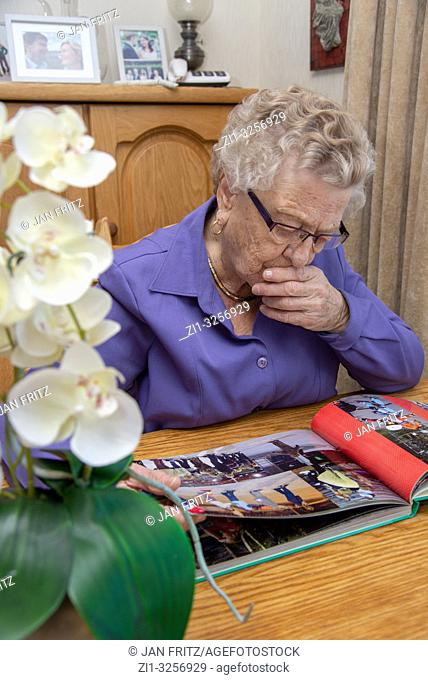 old woman looking at photoalbum