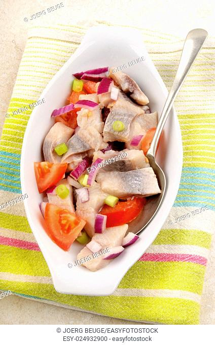 home made herring salad with tomato, purple onion and spring onions in a white bowl