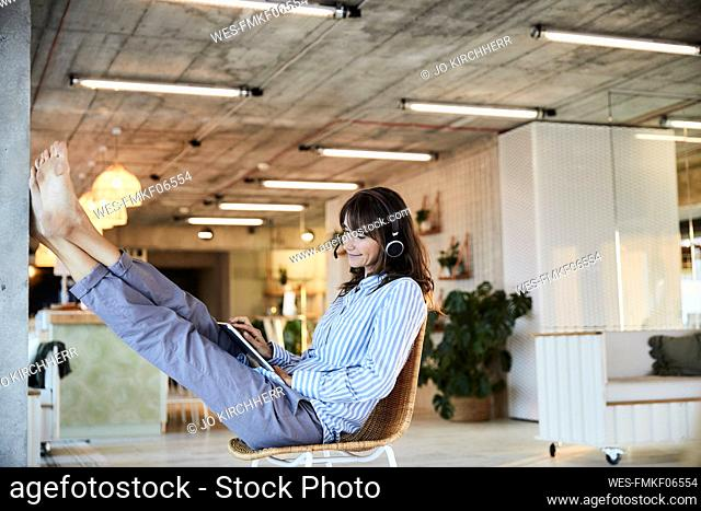 Mature woman listening to music while using digital laptop sitting on chair at home