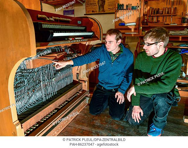 Konrad Scheffler (L), junior manager of the Organ Buidling business and the apprentice Richard Melzer speak next to an old organ console in their workshop in...