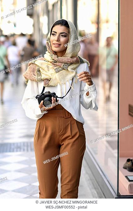 Spain, Granada, young Arab tourist woman wearing hijab, using fotocamera during shopping in the city