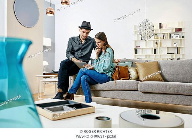 Couple choosing furniture in shop, using digital tablet