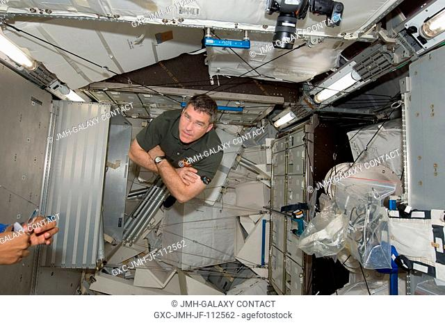 NASA astronaut Steve Bowen, STS-133 mission specialist, is pictured in the Permanent Multipurpose Module (PMM) of the International Space Station while space...