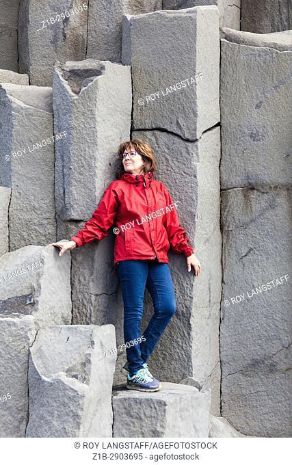 Tourist posing on the large basalt columns at Reynisfjara beach in Iceland