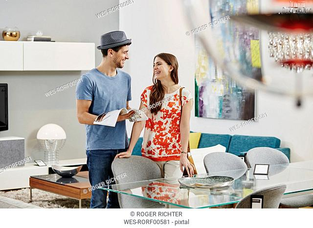 Couple in furniture store looking at dining table holding catalogue