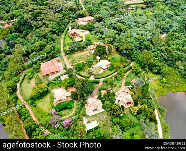 Aerial view of valley with lake, forest and villas in tropical country. Green mountain with forest on Brazil