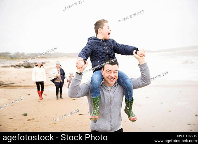 Happy father carrying son with Down Syndrome on shoulders on beach
