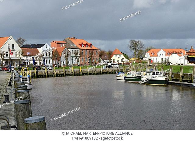 Buildings and houses and a street at the old harbour basin of Tönning with a few boats in it, 19 April 2016 | usage worldwide