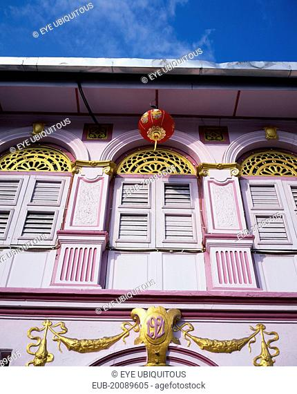Pink and gold painted shopfront with wooden window shutters and red and gold Chinese lantern hanging from the roof for Chinese New Year
